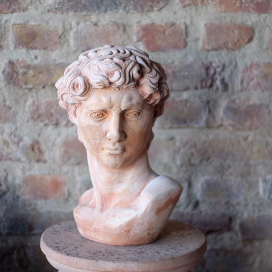 David Büste aus Teracotta auf Sockel vor Steinmauer