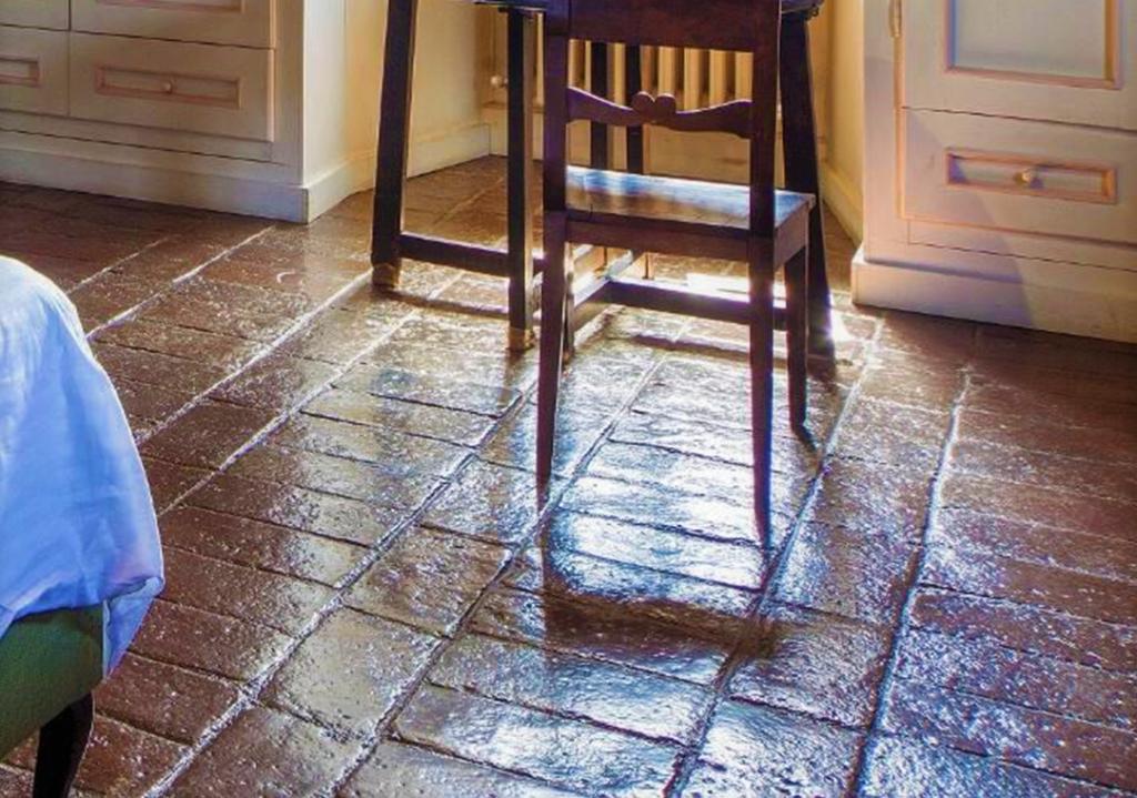 Ausschnitt eines Zimmers mit Stuhl und imprägnierten Cotto Fliesen